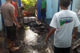 Petugas dan warga bergotong royong membersihkan rumah milik Suriyem yang terbakar, Rabu (22/1/2020). (Istimewa/BPBD Madiun)