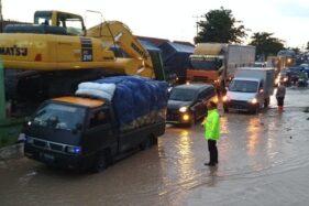 Polisi mengatur arus lalu lintas yang teradang banjir bandang di Desa Bumirejo, Kecamatan Margorejo, Kabupaten Pati, Jawa Tengah, Kamis (16/1/2020). (Antara-Akhmad Nazaruddin Lathif)