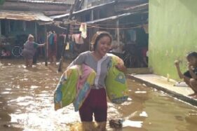 Warga korban banjir di Kota Pekalongan menyelamatkan harta benda menuju pengungsian, Minggu (26/1/2020). (Detik.com)