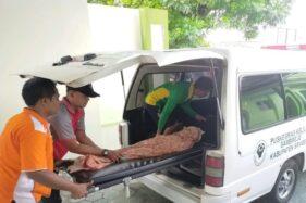 Jenazah Afis ditutupi jarit saat dimasukkan ke mobil jenazah untuk diantar ke rumah duka dari Puskesmas Sambirejo, Sragen, Jumat (24/1/2020). (Istimewa)