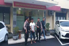 Personel Satuan Sabhara Polresta Solo membawa SY, warga Sukoharjo, yang tertangkap di Pasar Burung Depok untuk pemeriksaan lebih lanjut di Mapolresta Solo pada Minggu (26/1/2020) sore. (Ichsan Kholif Rahman)
