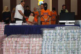 Polisi menghadirkan tersangka dan barang bukti uang saat ungkap kasus investasi ilegal Memiles di Polda Jawa Timur, Surabaya, Jawa Timur, Jumat (10/1/2020). (Antara-Didik Suhartono)