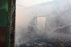 Seorang petugas Damkar memadamkan api yang membakar rumah warga Jogosetran, Kalikotes, Klaten, Minggu (19/1/2020). (Istimewa/Damkar Klaten)