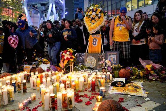 Sejumlah penggemar manaruh bunga dan lilin tanda penghormatan kepada Kobe Bryant di Microsoft Square, Los Angeles, AS, Minggu (26/1/2020) malam waktu setempat. (Reuters-Kyle Grillot)
