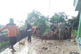 Petugas BPBD Kabupaten Kediri dibantu warga melakukan pembersihan dari sisa material tanah longsor di Desa Petungroto, Kecamatan Mojo, Kabupaten Kediri, Jawa Timur, Kamis (16/1/2020). (Antara)