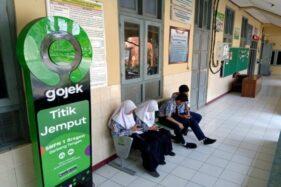 Sejumlah siswa menunggu jemputan ojol di kursi titik jemput yang disediakan Gojek sebagai wujud kerjasama Gojek dengan SMPN 1 Sragen, Jumat (24/1/2020). (Solopos/Tri Rahayu)