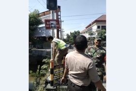 Tim gabungan Pemerintah Kecamatan Sukoharjo mencopot plamfet yang terpasang di traffic light simpang RSUD Ir Soekarno, Kamis (23/1/2020). (Solopos-Indah Septiyaning W.)