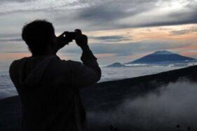 Seorang warga mengabadikan pemandangan saat matahari terbit di lereng Gunung Sindoro di kawasan wisata alam Posong, Kledung, Temanggung, Jawa Tengah. (Antara)