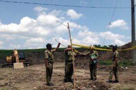 Sejumlah petugas tim gabungan Satpol PP Jateng memasang garis Satpol PP di lokasi tambang galian tanah uruk di Dukuh Tawangsari, Tunggul, Gondang, Sragen, Kamis (16/1/2020). (Istimewa/Satpol PP Sragen)