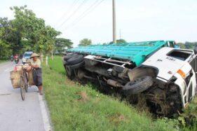 Pedagang keliling melintas di lokasi kejadian truk terguling di Jalan Pungkruk-Gabugan, Desa/Kecamatan Sidoharjo, Sragen, Sabtu (25/1/2020). (Solopos-Tri Rahayu)