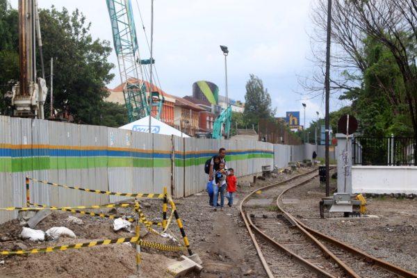 Calon penumpang kereta api (KA) berjalan menyusuri rel di dekat proyek pembangunan flyover Purwosari, Kerten, Laweyan, Solo, Kamis (27/2/2020). (Solopos/Nicolous Irawan)