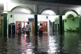 Sejumlah warga mengamankan alat elektronik dan barang-barang yang ada di musala Kelurahan Klegen, Kota Madiun, yang terendam banjir, Jumat (14/2/2020). (Abdul Jalil/Madiunpos.com)