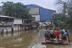 Warga kampung Petukangan Rawa Teratai menaiki perahu darurat menuju rumah mereka saat banjir di Jakarta Timur, Selasa (25/2/2020). Luapan Kali Mati menggenangi rumah dengan ketinggian 1-2 meter. (Antara-Fakhri Hermansyah)