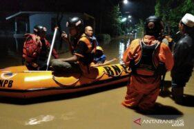 Petugas BPBD Jember akan mengevakuasi warga karena ketinggian banjir mencapai selutut orang dewasa di Kabupaten Jember, Jatim, Sabtu (22/2/2020). (Antara)