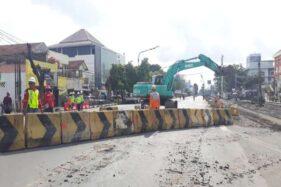 Eskavator mengusung beton pembatas saat penutupan Jl. Slamet Riyadi menuju perlintasan kereta api (KA) Purwosari, Solo, Rabu (5/2/2020). (Solopos-Nicolous Irawan)