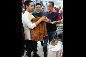 Gibran Rakabuming Raka (kiri) melipat kain batik bergambar ayahandanya, Presiden Joko Widodo (Jokowi), saat blusukan Beteng Trade Center (BTC) Solo, Senin (17/2/2020) siang. (Solopos/Kurniawan)