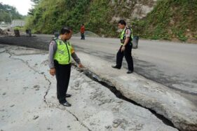 Petugas menunjukkan kondisi Jalan Raya Ponorogo-Pacitan Km 227, Desa Wates, Kecamatan Slahung, Ponorogo, yang ambles, Senin (1/4/2019). (Istimewa-Polsek Slahung)