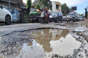 Kubangan jalan berlubang di kawasan simpang tiga Tugu Lilin, Pajang, Laweyan, Solo, semakin parah karena peningkatan jumlah kendaraan melintas, Minggu (16/2/2020). (Solopos/Indah Setiyaning w.)
