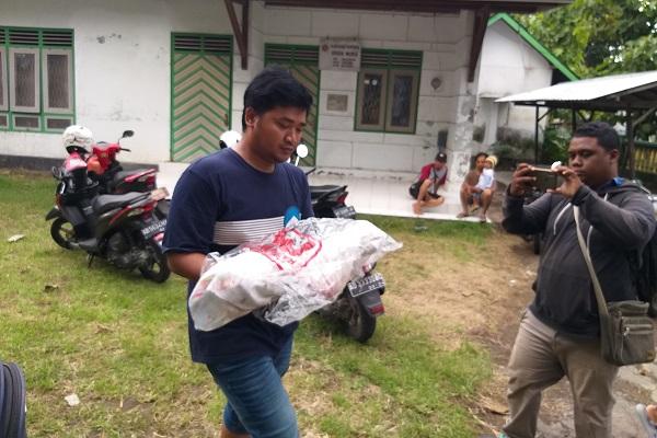 Bayi laki-laki yang dibuang di saluran irigasi dibawa petugas dengan ditutup kain dan plastik di Bendo, Daleman, Tulung, Sabtu (8/2/2020). (Solopos-Ponco Suseno)