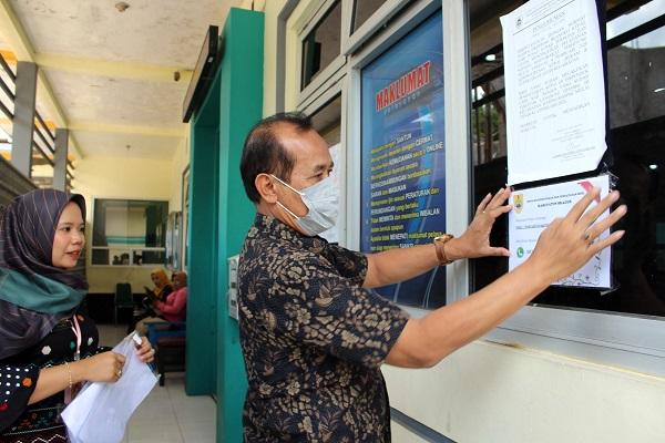 Kepala Dispendukcapil Sragen Haryatno Wahyu Lwiyanto memasang pengumuman pelayanan adminduk secara online di depan kantor pelayanan Dispendukcapil Sragen, Kamis (19/3/2020). (Solopos/Tri Rahayu)