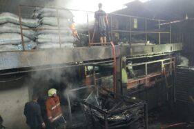 Petugas pemadam kebakaran dibantu warga sekitar berupaya memadamkan api yang membakar oven briket milik pabrik arang CV Sastro Briko di Jaten pada Minggu (29/3/2020). (Istimewa)