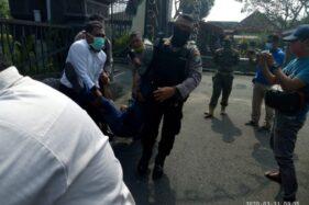 Petugas menangkap Slamet Ridwan, wartawan yang menghadang arak-arakan mobil dinas Bupati Tulungagung Maryoto Birowo di depan pendopo Kabupaten Tulungagung, Selasa (31/3/2020). (Antara/Ist)