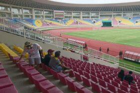 Suporter Persis Solo membersihkan kursi di tribune Stadion Manahan. (Solopos.com/Chrisna Chanis Cara)