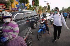 Wali Kota Madiun, Maidi, menyemprot disinfiktan di jalan-jalan untuk mencegah persebaran virus corona, Jumat (27/3/2020). (Istimewa-Pemkot Madiun)