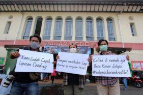 Pewarta foto Solopos berfoto menyerukan setop hoaks di depan Pasar Gede Solo yang beroperasi normal, Selasa (24/3/2020). (Solopos)