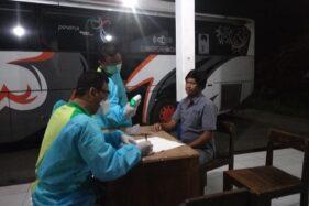 Seorang pemudik (kanan) diperiksa kesehatannya oleh tim.gabungan di posko Terminal Pilangsari, Ngrampal, Sragen, Kamis (2/4/2020) dini hari. (Istimewa/Dishub Sragen)