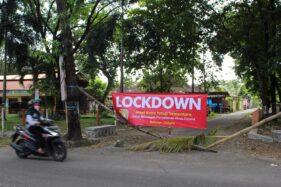 Seorang pengendara motor melintas di depan gang masuk yang diblokade pakai spanduk lockdown di Kampung Beloran, Sragen Kulon, Sragen, Kamis (16/4/2020). (Solopos/Tri Rahayu)