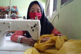 Seorang siswi SMKN 4 Kota Madiun menjahit baju APD di ruang menjahit sekolah itu, Senin (6/4/2020). Baju APD pesanan Pemprov Jatim. (Abdul Jalil/Madiunpos.com)