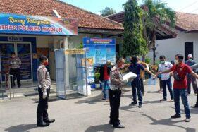 Para pemohon SIM berolahraga sebelum masuk ke ruangan Satpas Polres Madiun, Kamis (9/4/2020). (Abdul Jalil/Madiunpos.com)