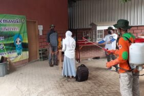 Sukarelawan dari LPBI NU Kota Madiun menyemprotkan antiseptik di tubuh santri Ponpes Al Mujaddadiyah, Kelurahan Demangan, Kecamatan Taman, Kota Madiun, yang akan pulang, Selasa (31/3/2020). (Abdul Jalil/Madiunpos.com)
