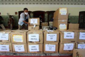 Petugas menata kardus berisi bantuan alat pelindung diri (APD) untuk tenaga medis yang menangani kasus corona dan handsanitizer di halaman depan Loji Gandrung, Solo, Jumat (10/4/2020). (Solopos/Nicolous Irawan)
