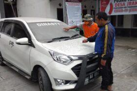 Seorang warga Desa Jrakah, Selo, Boyolali, menunjukkan abu tipis yang mengotori mobil akibat erupsi Merapi, Jumat (10/4/2020) siang. (Istimewa)