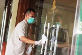 Petugas Housekeeping membersihkan gagang pintu di The Sunan Hotel Solo. (Istimewa)