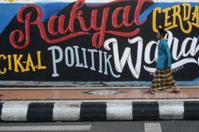 Warga berjalan di depan mural bertuliskan pesan politik di Kudus, Jateng, Selasa (9/1/2018). (JIBI/Solopos/Antara/Yusuf Nugroho)