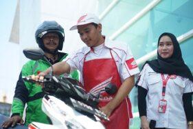 Ilustrasi seorang Service Advisor (SA) dan mekanik yang sedang menerima sepeda motor dari konsumen yang berprofesi sebagai driver ojek online. (Istimewa)