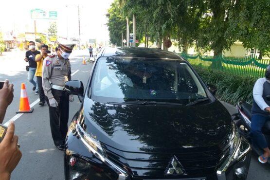 Anggota polisi menghentikan laju kendaraan roda empat berpelat nomor dari Jabodetabek di Prambanan, Klaten, Jumat (8/5/2020). (Solopos/Ponco Suseno)
