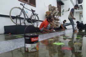 Sejumlah seniman cat Indaco mengecat lantai Rutan Solo. (Istimewa)