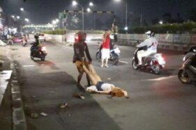 Seorang wanita tergeletak di jalan di  di depan gedung bekas Kampus LP3I Pasar Minggu, Jakarta. (Suara.com)