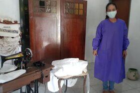 Pemilik industri kecil suvenir tas, Elisa Candra Kartikawati, mencoba baju hazmat produksinya, Kamis (25/6/2020). (Abdul Jalil/Madiunpos.com)