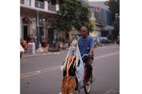 Lelaki paruh baya dengan boneka pengantin melintas di depan Pasar Gede Solo (Instagram/@supersoklat).