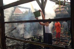 Warga menyiramkan air ke sisa bangunan yang terbakar di Dusun Karangwidoro RT 001, RW 002, Desa Guci, Kecamatan Godong, Kabupaten Grobogan, Sabtu (6/6/2020) sore. (Istimewa/Polsek Godong)