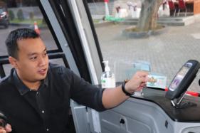 Warga menggunakan Mandiri e-money untuk membayar tarif bus di Solo. (Istimewa)
