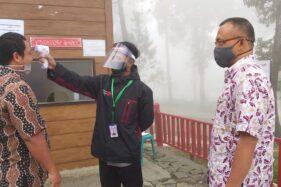 Petugas di pintu masuk objek wisata mengecek suhu pengunjung yang hendak masuk ke lokasi objek wisata di Tawangmangu, Rabu (1/7/2020). Istimewa-Perum Perhutani KPH Surakarta