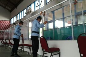 Petugas Rutan Solo merapikan bilik kunjungan persiapan kenormalan baru di aula Rutan Solo pada Kamis (9/7/2020) siang. (Solopos/Ichsan Kholif Rahman)
