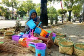Paiyem, 80, menjajakkan sapu lidi, gayung dan tumbu di depan SPBU Sine, Sragen, Jumat (10/7/2020). (Solopos/Moh. Khodiq Duhri)