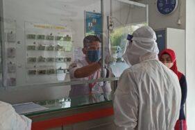 Seorang petugas tengah memeriksa suhu tubuh pengunjung yang datang di salah satu perusahaan di lingkungan Kawasan Industri Wijayakusuma, Kota Semarang, Kamis (9/7/2020). (Semarangpos.com-Humas PT KIW)